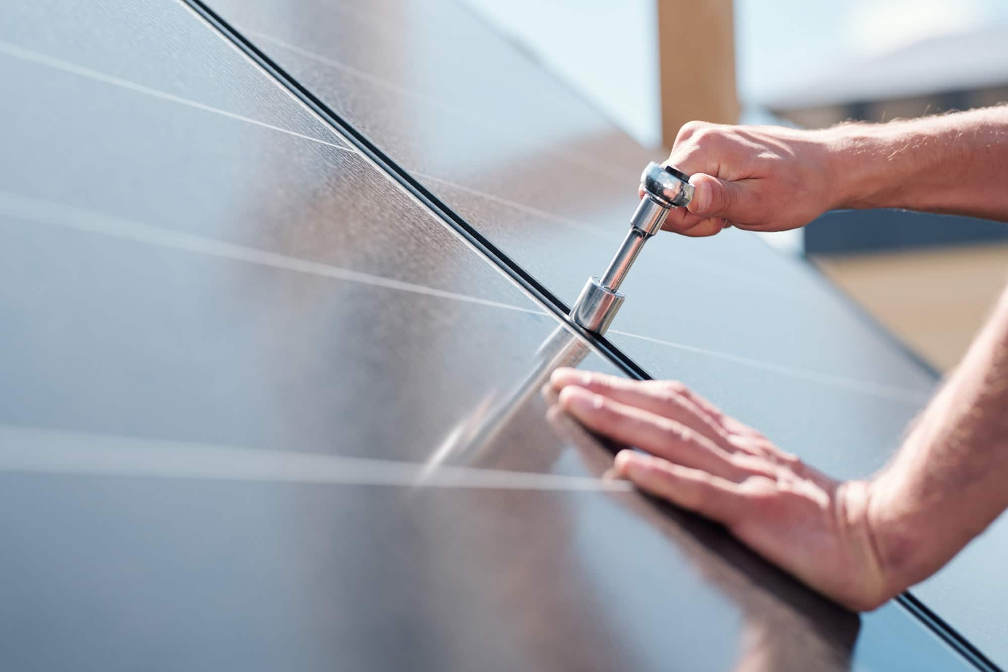 Hands of contemporary master with screw adjusting or installing solar panels
