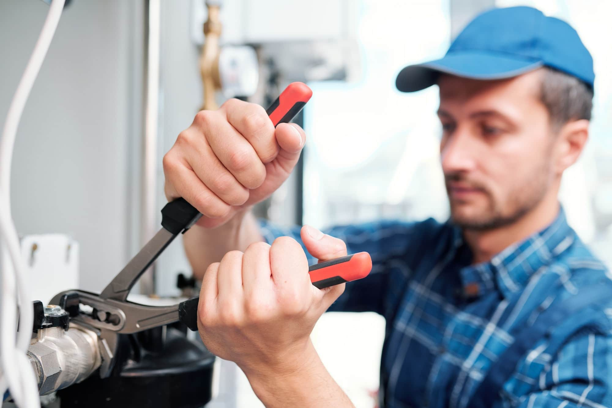 Hands of young contemporary technician with pliers fixing nut on pipe
