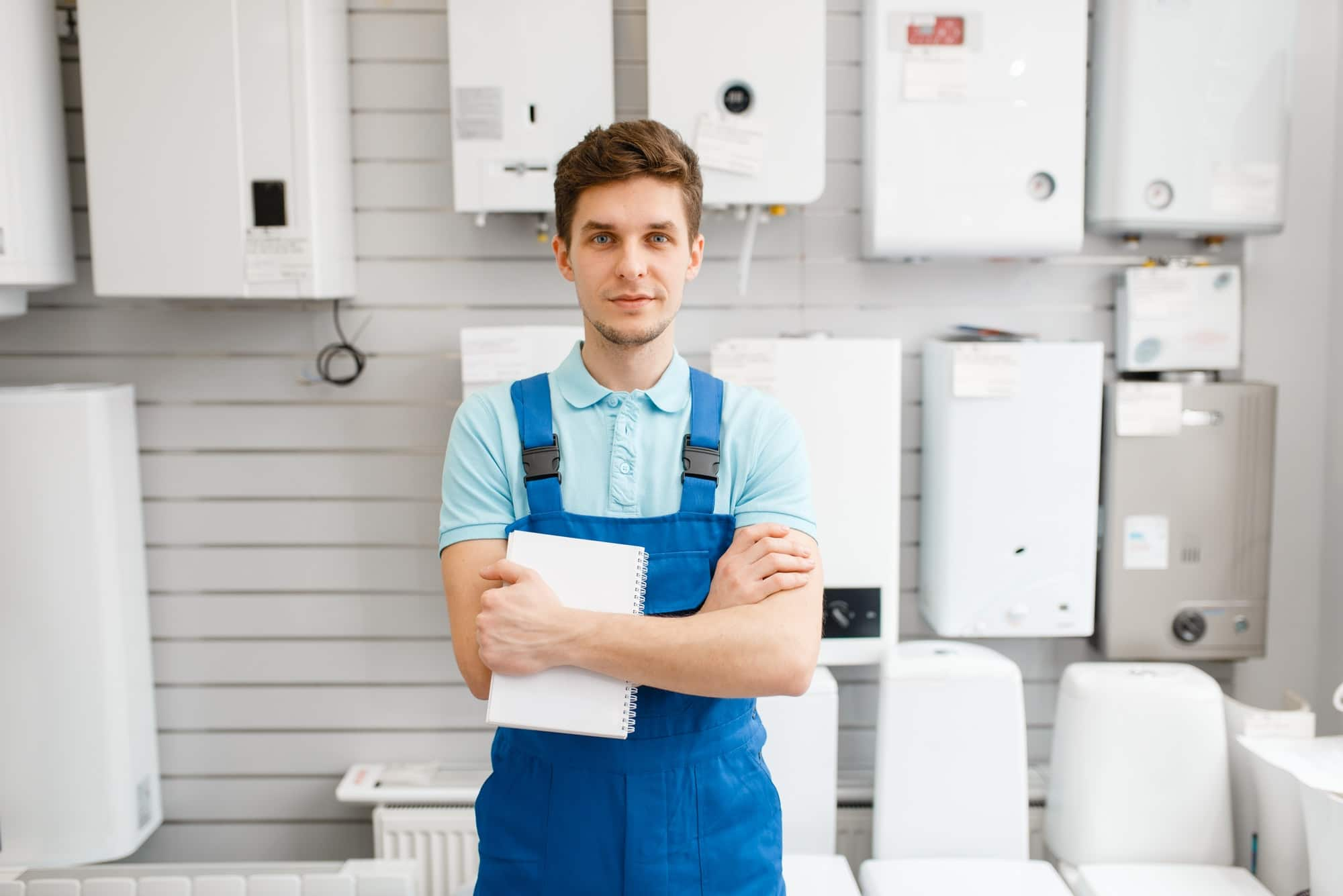 Plumber at showcase with boilers, plumbering store
