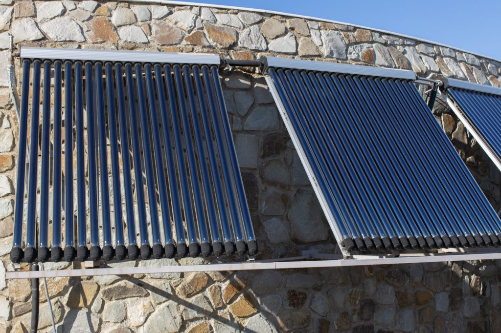 Solar water heating system installed on wall or roof of house.