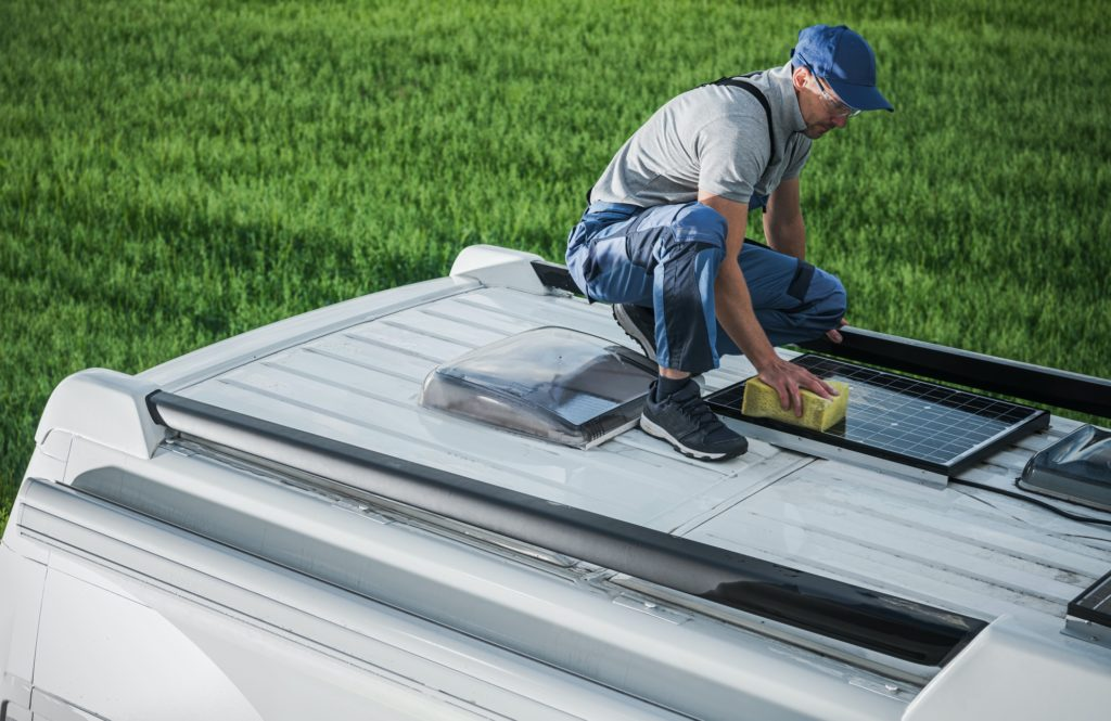Man Cleaning Roof Installed Solar Panels