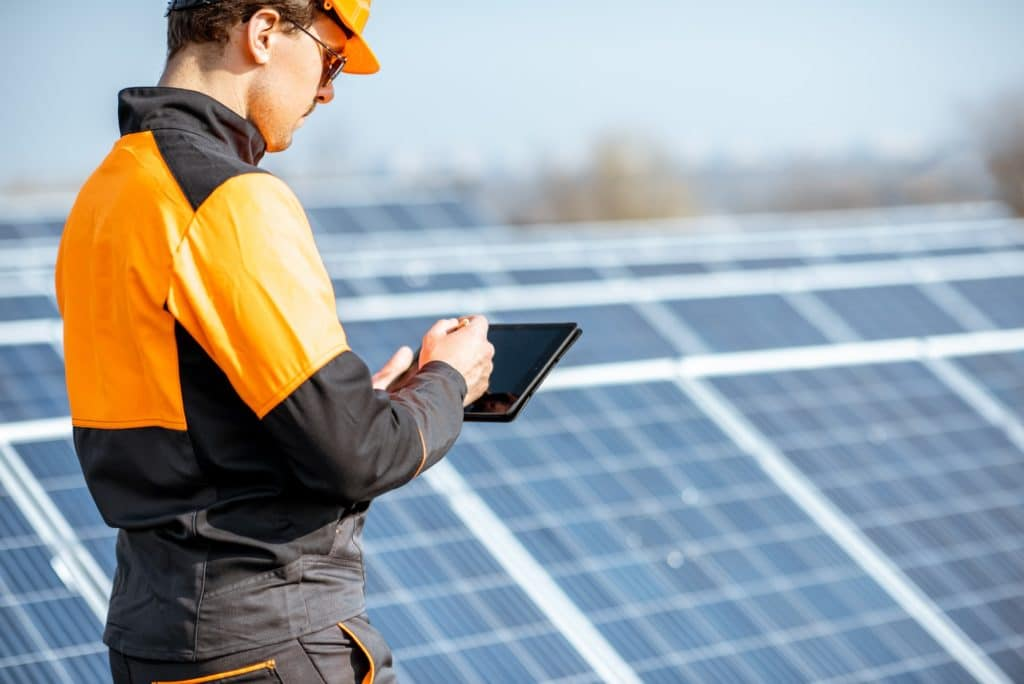 Engineer servicing solar panel on electric plant